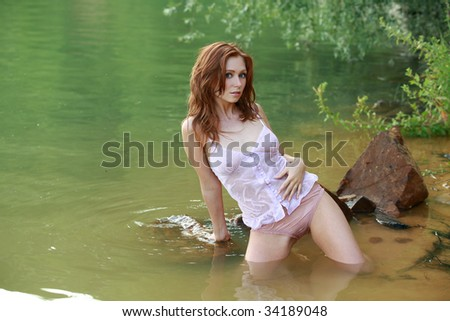 Girl with red hair in the water - stock photo
