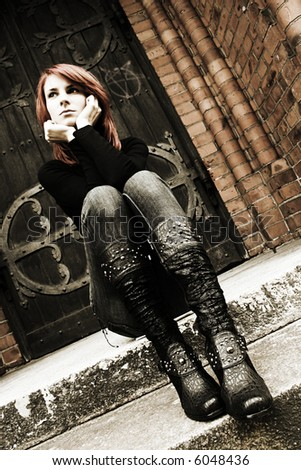 girl with red hair is sitting on the stairs (sepia)