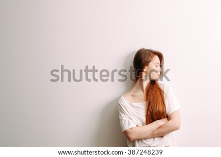 Girl with red hair standing on a white background. Face in profile