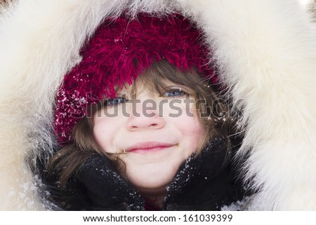 Girl with red hat and fur clothes - stock photo