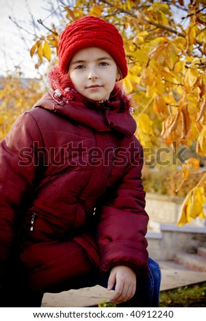 Girl with red hat at autumn - stock photo