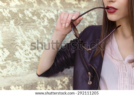 girl with red lipstick in a black leather jacket sunglasses bit in city - stock photo