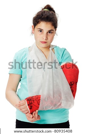 Girl with red plaster cast and sling, looking sadly into the camera. Studio shot against a white background. - stock photo