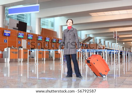 girl with red suitcase standing in airport hall - stock photo