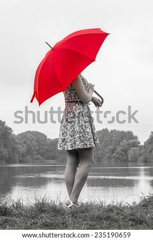 Girl with red umbrella stands near the pond