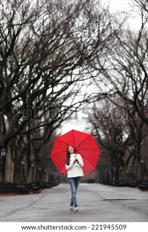 Girl with red umbrella walking in park in fall. Happy smiling multiracial Asian woman walking cheerful with red umbrella in Central Park, Manhattan, New York City, USA. - stock photo