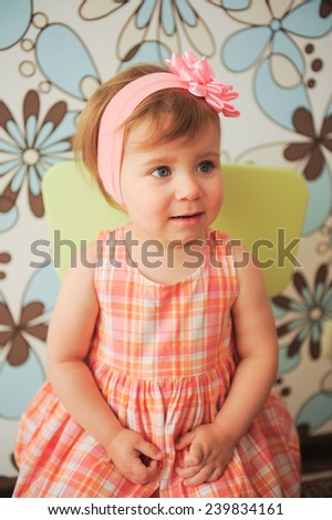 girl with rose headband sitting on chair - stock photo