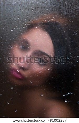 girl with sad eyes behind frosted glass - stock photo