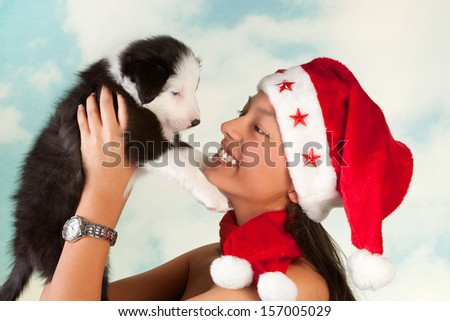 Girl with santa hat holding a cute little border collie puppy - stock photo