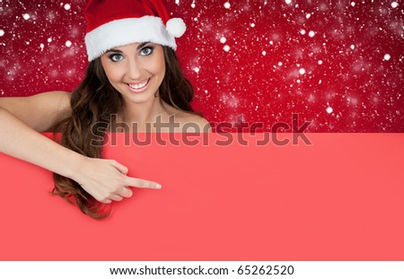 girl with santa hat on snow behind blank board pointing - stock photo