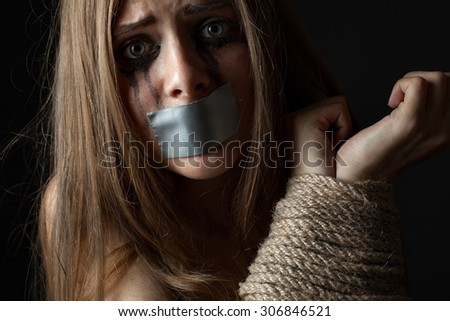 Girl with sealed  mouth and bound hands. Victim or hostage.  Closeup - stock photo