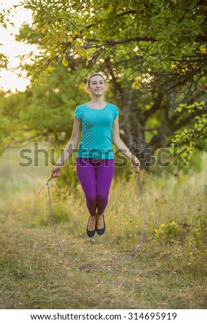 girl with skipping rope training on the nature
