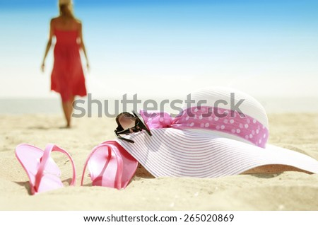 Girl with slippers and a hat on a beach - stock photo