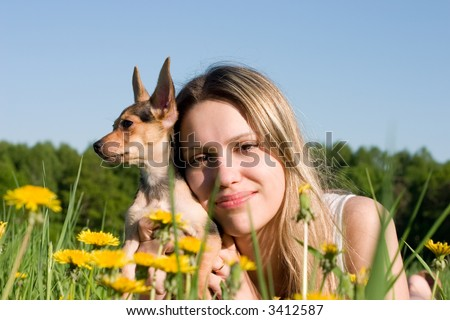 girl with small doggy on glade with dandelions