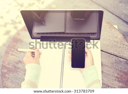 Girl with smartphone, blank diary with pen and laptop on a wooden table - stock photo