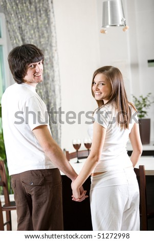 Girl with smile and boy on kitchen - stock photo