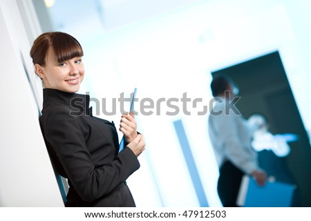 Girl with smile in black jacket with blue folder - stock photo