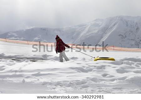 Girl with snow tube at sun gray day. Caucasus Mountains, Georgia. Ski resort Gudauri. - stock photo