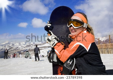 Girl with snowboard on the top of mountain