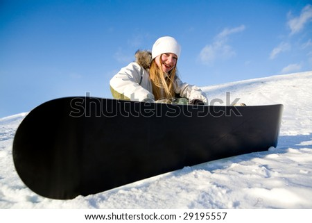 Girl with snowboard sit on snow