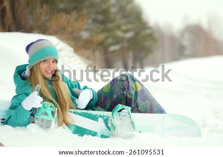 Girl with snowboard sitting on the snow - stock photo