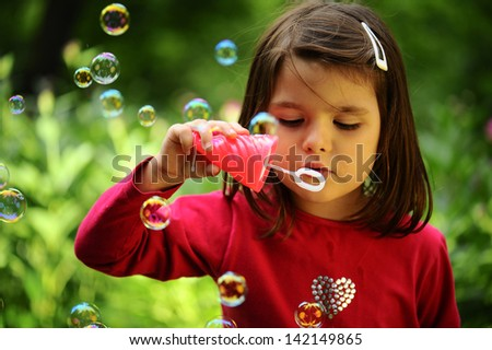 Girl with soap bubbles in  park. - stock photo