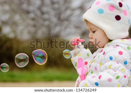 girl with soap bubbles in spring time - stock photo