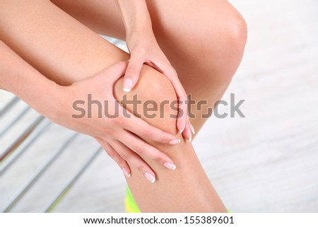 Girl with sore foot on gray background - stock photo