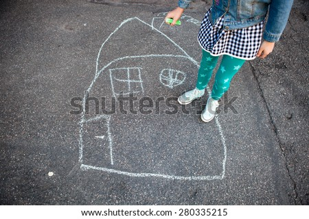 Girl with street chalk outdoors and a drawing of a house on asphalt
