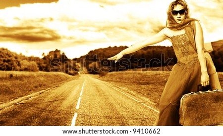 girl with suitcase stops the car on road - stock photo