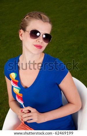 Girl with sunglasses and a lollipop sitting on a Swivel chair - stock photo
