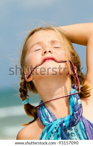 Girl with sunglasses in her mouth at the beach - stock photo