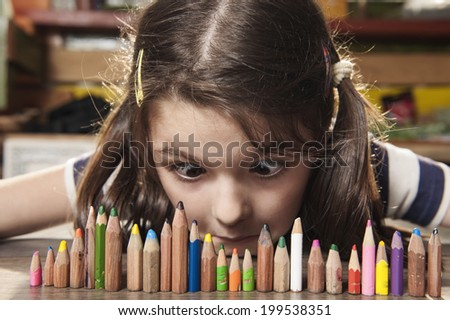Girl with surprise looks at pencils - stock photo