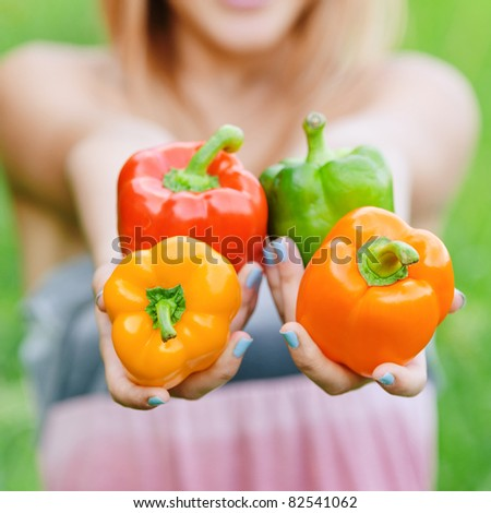 Girl with sweet pepper, on green summer background. - stock photo
