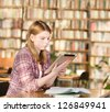girl with tablet computer in library - stock photo