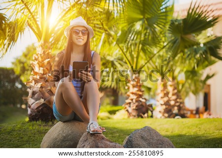 girl with tablet in the palm garden - stock photo