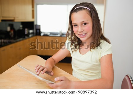 Girl with tablet sitting at the kitchen table - stock photo