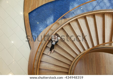 girl with tablet sitting on the spiral wooden staircase