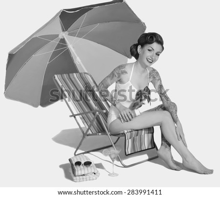 Girl with tattoos apply suntan lotion on the beach. Retro Style - stock photo