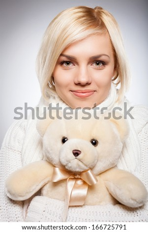 Girl with Teddy bear. Beautiful young blond hair woman holding a teddy bear and smiling while isolated on grey - stock photo