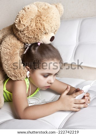 Girl with Teddy bear lying together looking at mobile phone - stock photo