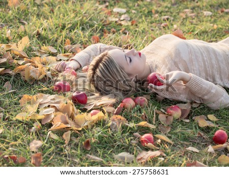 Girl with the apple is lying on the grass - stock photo