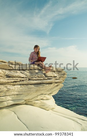 Girl with the computer on the rocks - stock photo