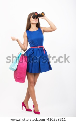 Girl with the shopping bags looking through the binoculars - stock photo
