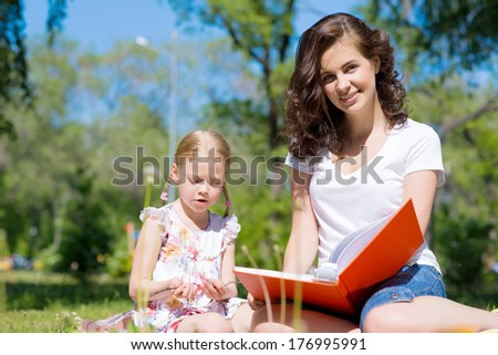 girl with the teacher reading a book together in the summer park - stock photo
