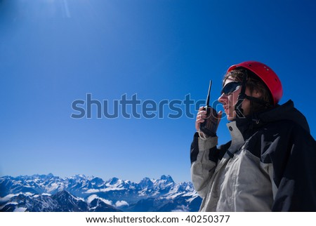 Girl with the wireless station speaks on  background mountain landscape