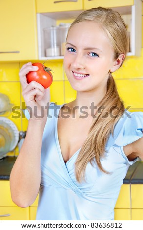 girl with tomatoes in the kitchen - stock photo
