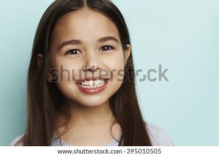 Girl with toothy smile in blue studio