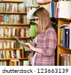 girl with touchpad in library - stock photo