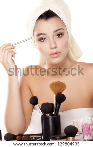 girl with towel on head draws her eyebrows with a Eye brow brush - stock photo